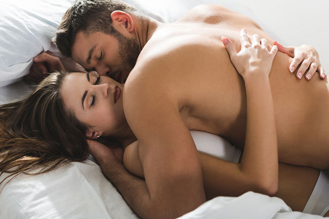 image of a man and woman embracing in bed in an intimate way