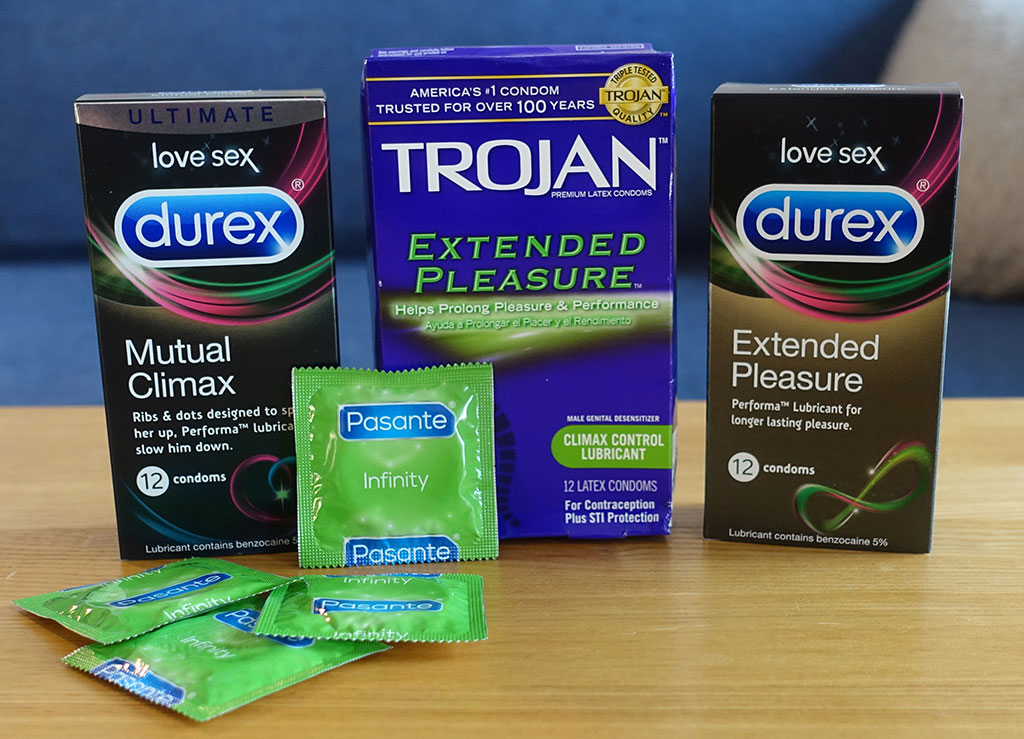 photo of four different brands of benzocaine condom - trojan, pasante, durex mutual climax and extended pleasure