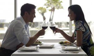 man turning a woman on at the dinner table by flirting
