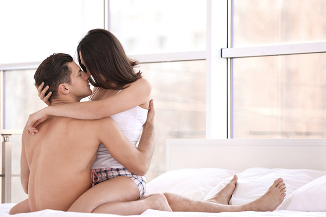 sensual photo of a couple in bed kissing