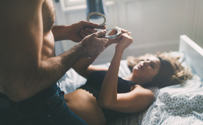 photo of a man and woman playing a domination game in bed