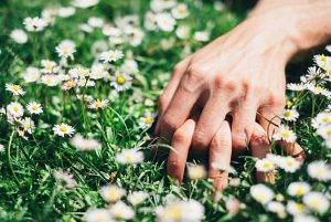 image of two hands interlocked in a field to represent sex outdoors