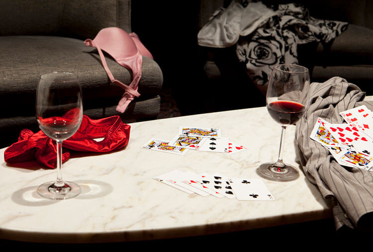 cards on a table with clothes around as if playing a game of strip poker