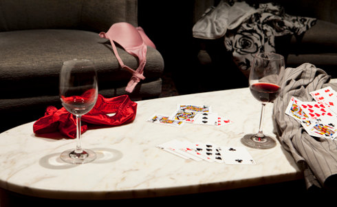 image of a game of strip poker with cards, wine and clothes on the floor