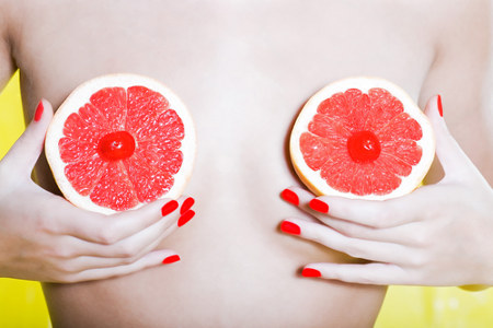fun photo of a woman holding fruit in front of her body to represent nipples