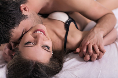 photo of a man kissing a woman in bed
