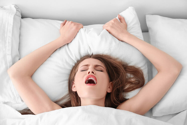 photo of a woman's head above the bed covers with a look of having an orgasm