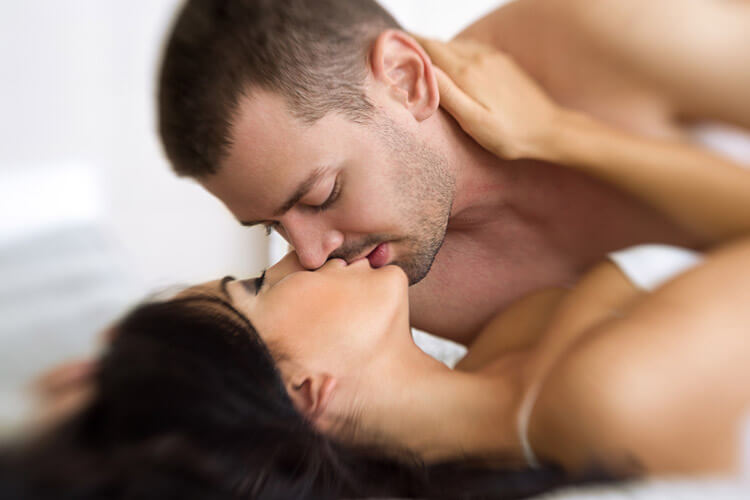 man and woman kissing as part of foreplay