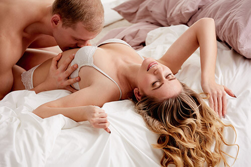 image of a man kissing a woman on a bed erotically